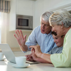 Grandson using laptop with grandparents at home